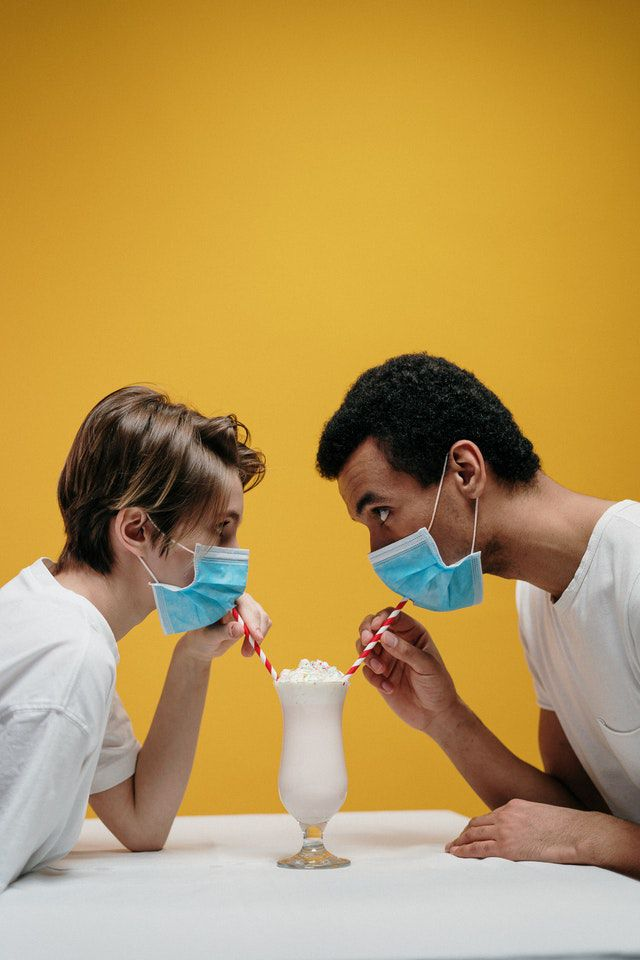 A man and woman drinking milkshake with masks on so they can start dating someone with bad breath.
